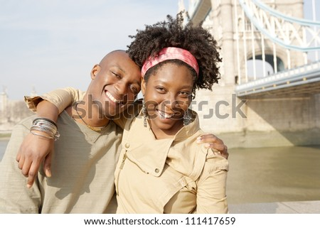 Young attractive black couple having fun while visiting the Tower of London and smiling. - stock photo