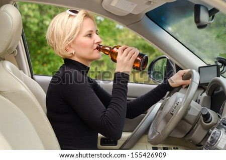 Young attractive blond female driver drinking alcohol from a bottle and driving sitting inside the car behind the steering wheel - stock photo