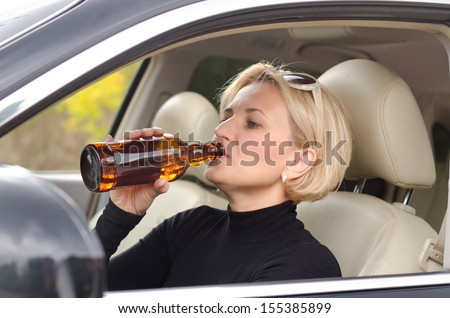 Young attractive blond female driver drinking alcohol from a bottle and driving the car with a smile of enjoyment on her face as she poses a threat to other road users - stock photo