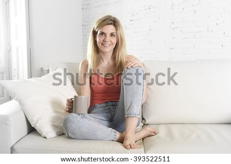 young attractive blond hair woman holding cup of coffee sitting on sofa couch at home living room smiling happy and relaxed lifestyle concept