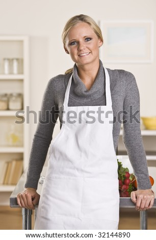 Young attractive blond with apron in the kitchen, leaning on the counter. - stock photo