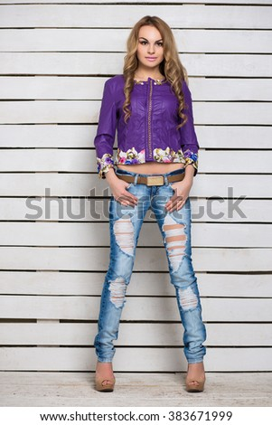 Young attractive blond woman in ripped jeans and purple jacket posing near the white wooden wall - stock photo