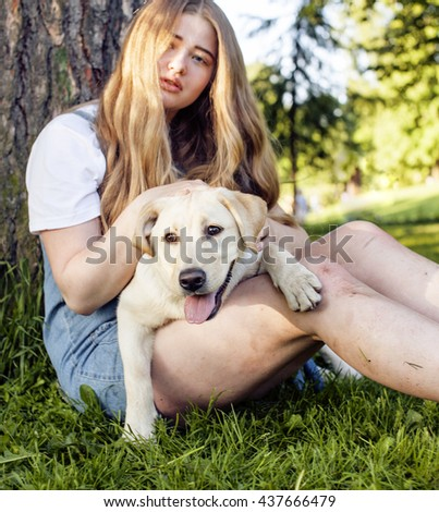 young attractive blond woman playing with her dog in green park at summer, lifestyle people concept, true friendship - stock photo