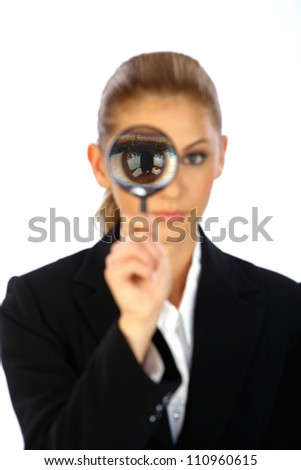 Young attractive blonde business girl holding magnifying glass in front of her eye close up