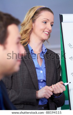 Young attractive blonde businesswoman standing next to flip chart, very positive face expression - stock photo