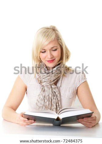young attractive blonde female student checks something in her book, isolated on white