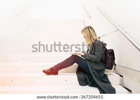 young attractive blonde female student learning on-line on her laptop while sitting on the steps.copy space area for your text message or content - stock photo