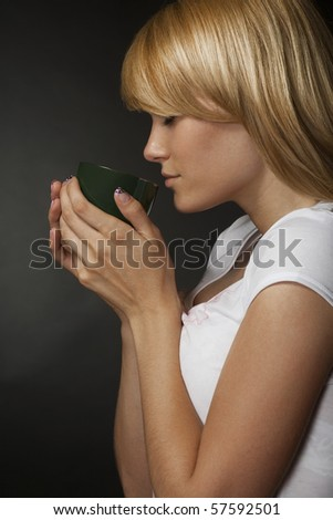 Young attractive blonde girl enjoys a cup of fragrant coffee. It is removed in studio on a grey background - stock photo