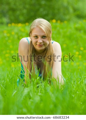 Young attractive blonde girl is relaxing in the park
