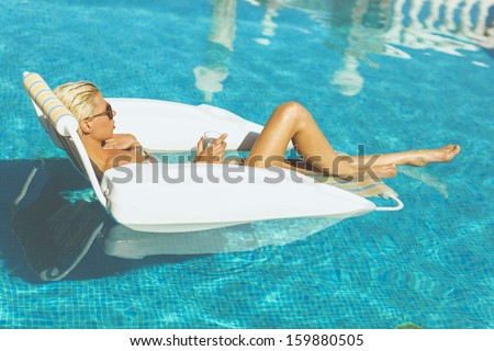 Young attractive blonde holding a glass of water and relaxing in pool on a hot summers day - stock photo