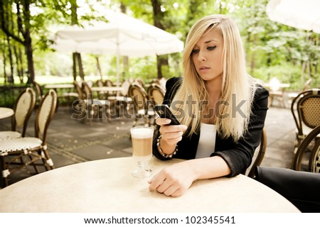Young attractive blonde sending messeges in the restarurant - stock photo