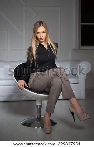 Young attractive blonde wearing business clothes sitting on a chair - stock photo