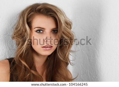 Young attractive blonde woman looking at camera studio portrait - stock photo