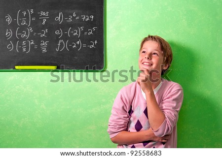 Young attractive boy standing in front of blackboard with wondering face expression. - stock photo