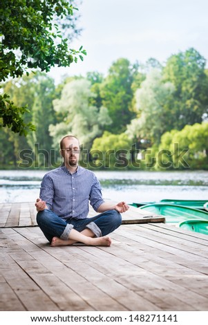 Young attractive breaded man with closed eyes sitting on wooden pier, relaxing and meditating in summer morning - stock photo