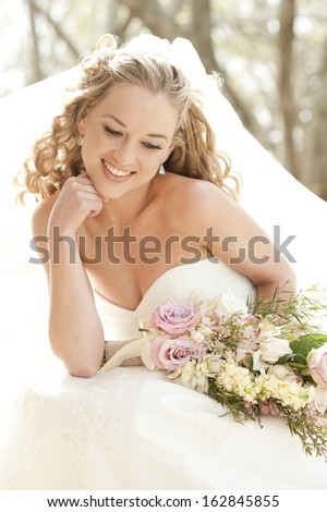 Young attractive bride sitting with bouquet of flowers smiling - stock photo