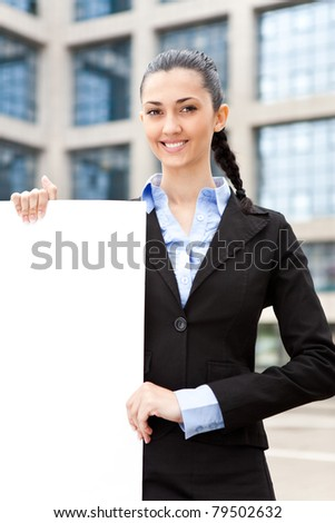 young attractive brunette businesswoman holding big blank paper - stock photo