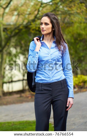 young attractive brunette businesswoman in park, wears blue shirt and grey suit, outdoor shoot - stock photo