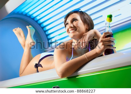 Young attractive brunette girl is laying in the working solarium - stock photo