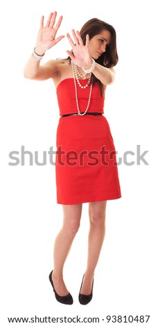 Young attractive brunette in red dress makes stay away, stop gesture, studio shoot isolated on white - stock photo
