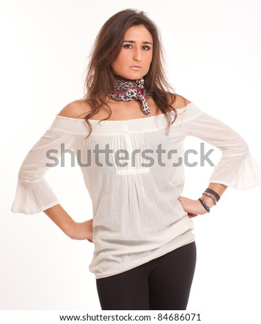 Young attractive brunette with a serious expression and hands on hips - stock photo