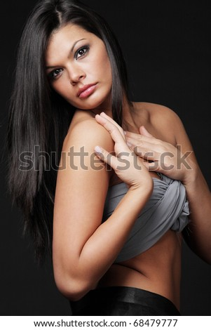 Young attractive brunette with long hair posing on black background. - stock photo