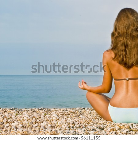 Young attractive brunette woman in swim suit doing yoga moves or meditating on sea beach - stock photo
