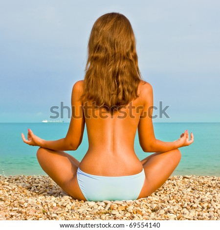Young attractive brunette woman in swimming trunks doing yoga moves or meditating on sea beach - stock photo