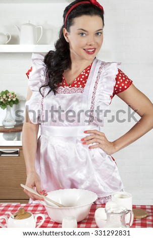 Young attractive brunette woman standing by the table in the kitchen, cooking the meal - stock photo