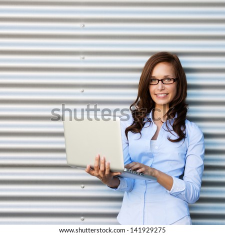 Young attractive brunette woman wearing glasses holding a laptop smiling at the camera. - stock photo