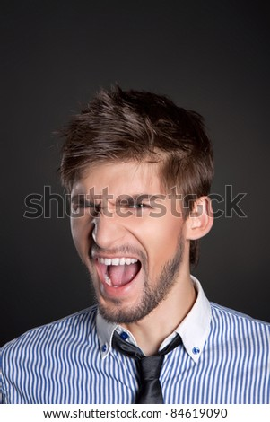 Young attractive business man emotional scream over gray background. - stock photo