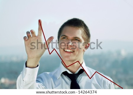 young attractive business man pointing to a red chart line outdoors