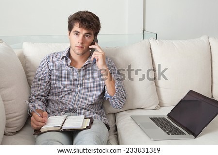Young attractive business man sitting on a white sofa in his home living room, making a call on his smartphone and using a laptop computer. Professional businessman working from home, sitting on sofa. - stock photo