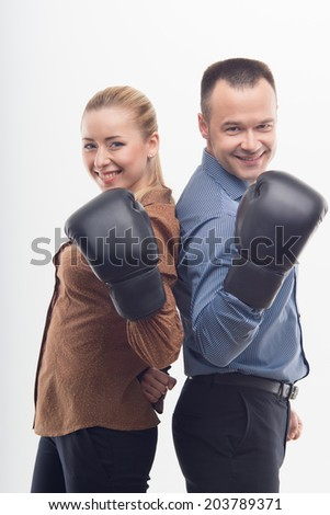 Young attractive business woman and man with boxing gloves standing back to back, isolated on white background - stock photo
