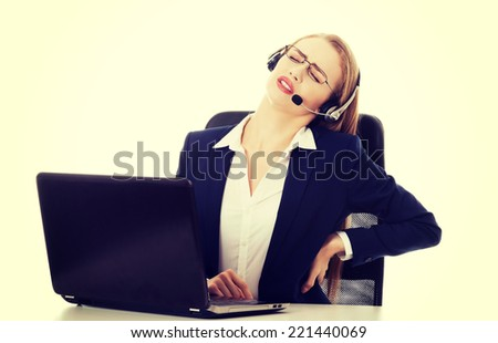 Young attractive business woman at call center is having backache. Isolated on white. - stock photo