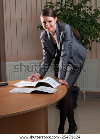 Young attractive business woman in a office environment makes notes in an album with drawings