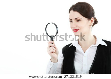Young attractive business woman looking into a magnifying glass, isolated on white background - stock photo