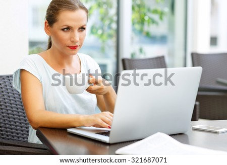 Young attractive business woman sitting in a cafe with a laptop and drinks her morning coffee - stock photo