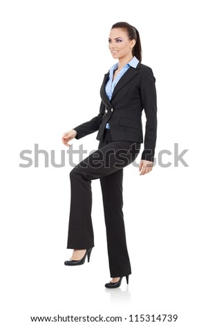Young attractive business woman stepping on imaginary step and looking away from the camera, upwards, suggesting progress