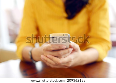 Young attractive business woman using cellphone at a restaurant - stock photo