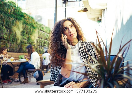 Young attractive business woman with curly hair holds a job interview in a coffee-shop.beautiful girl takes a journalist interviews.Portrait of a beautiful businesswoman talking on the smart-phone. - stock photo