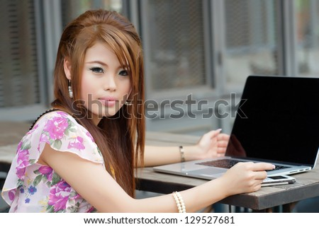 Young attractive business woman working on her laptop at outdoors cafe - stock photo