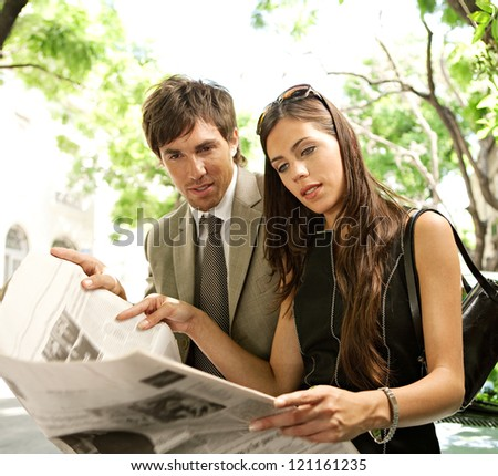 Young attractive businessman and businesswoman standing together and sharing a newspaper in a tree aligned street in a classic city, smiling. - stock photo