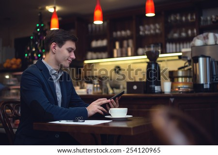 Young attractive businessman in a suit drinking coffee and using tablet to read news. - stock photo