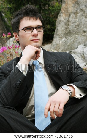 Young attractive businessman in a suit looks off into the distance. - stock photo