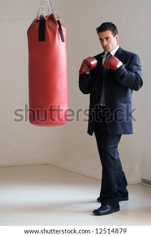 Young attractive businessman in a suit wearing boxing gloves standing ready in front of a heavy punching bag - stock photo