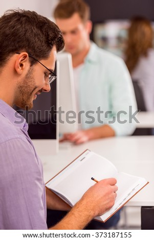Young attractive businessman in casual clothes and eyeglasses writing, in the background people working in office