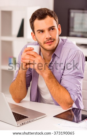 Young attractive businessman in casual clothes drinking coffee and dreaming while working in office - stock photo