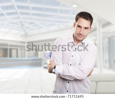 Young attractive businessman in corporate building - stock photo