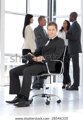 Young attractive businessman in office working - stock photo